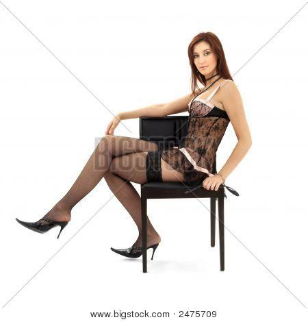 Morena de renda preta na cadeira com máscara