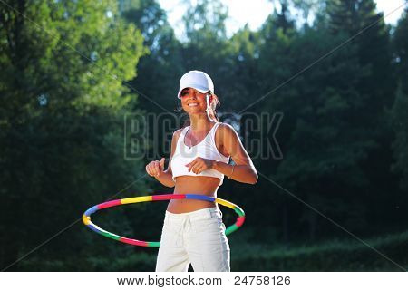 woman rotates hula hoop on nature background