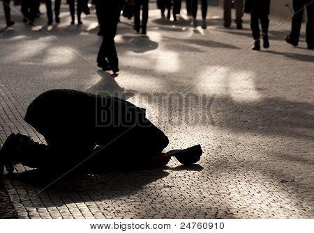 Beggar Kneeling On A Pavement