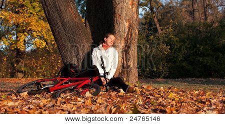 Woman Cyclist Sits Leaning Against A Tree And Enjoy Recreation