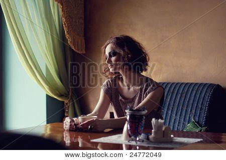Fine art photo of a gorgeous brunette woman sitting alone near a window