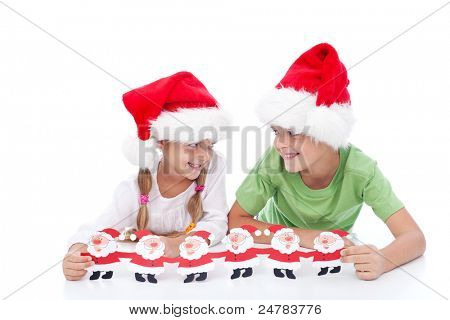 Mischievous christmas kids waiting for santa holding paper decoration