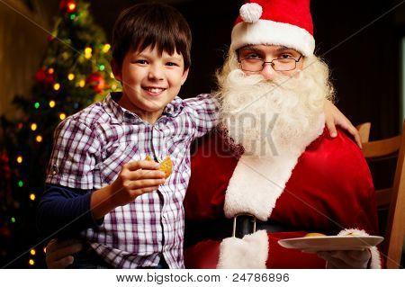 Photo of cute boy and Santa Claus looking at camera