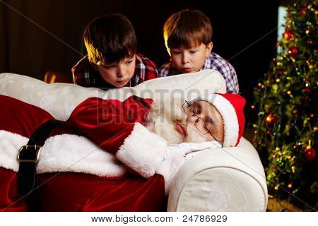 Photo of Santa Claus sleeping on sofa with two amazed kids looking at him