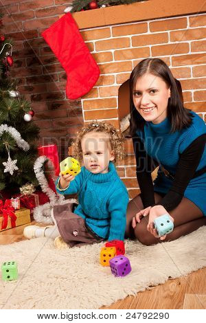 Mother and her daughter near Christmas tree