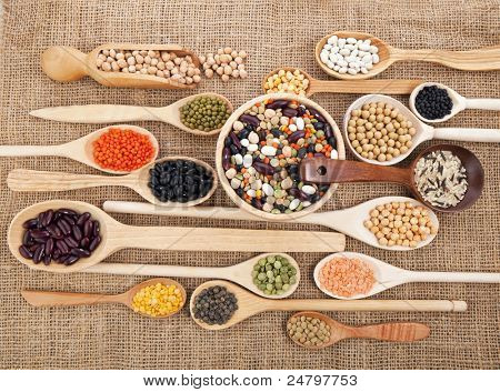 Mix from different beans, legumes, peas, lentils in spoon on the sackcloth background