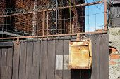 A High Wooden Fence With A Old Rusty Mailbox, Bricks Wall poster