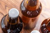 Close Up High Angle View Of Unlabelled Bottles Of Craft Beer With Focus To The Cap On A Single Bottl poster