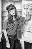 Girl In Hippy Head Band Standing Next To Shelf. Woman In Multi Layered Boho Style Clothes. Model Wit poster