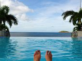 stock photo of infinity pool  - Woman relaxing at infinity pool at luxury resort on St. Thomas US Virgin Island (USVI)