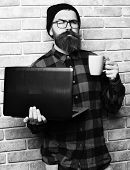 Brutal Caucasian Serious Unshaven Hipster Holding Laptop With Mag Or Cup In Red Black Checkered Shir poster