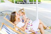 Happy Mother And Daughter Kissing Each Other During Relaxing In The Deckchair In The City Park Recre poster