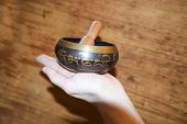 Brass Singing Tibetan Spiritual Bowl  On  Wooden Background Healing Sound With Hand poster