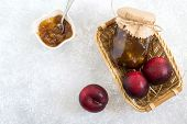 Jar Of Homemade Jam From Plums In Wicker Basket, Large Red Plums And Saucer With Jam On Gray Stone B poster