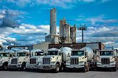 A Range Of Cement Mixer Trucks  In A Parking Lot Of A Cement Factory. poster