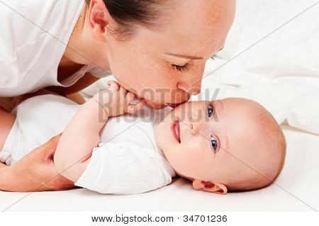 picture of happy mother with adorable baby. mother kissing her baby