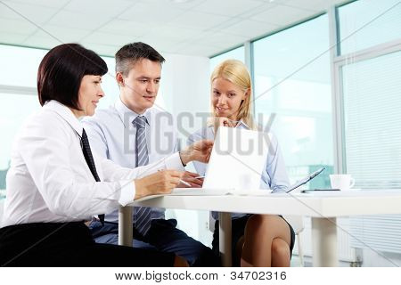 Three business partners sitting in office and working with computer