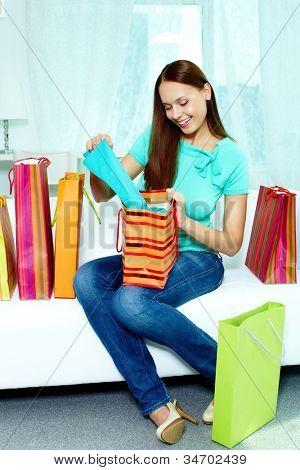 Retrato do cliente feliz sentado no sofá depois de compras e olhando através de compra