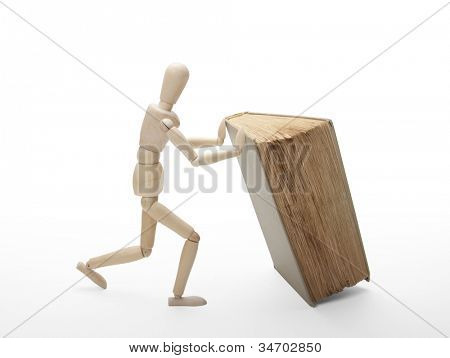 Wooden man and book, isolated on white