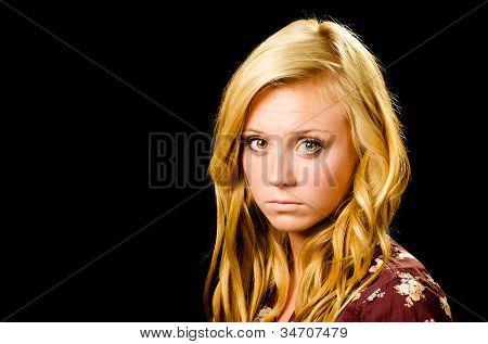 Portrait of pretty teenage girl looking sad or depressed isolated on black