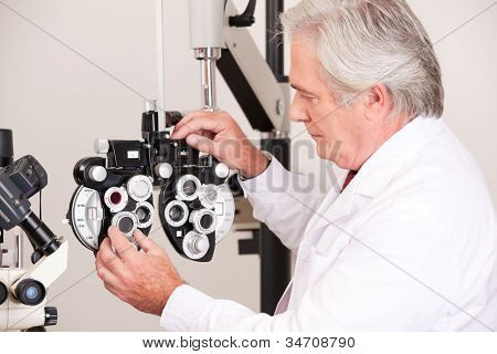 Doctor in ophthalmology clinic adjusting phoropter.