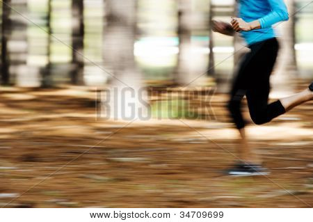 Action motion shot of runner training in forest with blur to show speed and sprinting.