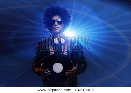 Dj with vinyl record in club wearing sunglasses listening to party music and lens flare