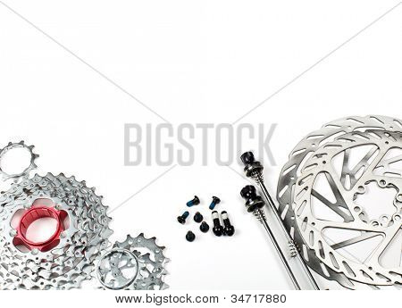 Mountain bike rear cassette, bolts, skewers and disk rotors on white background