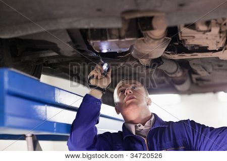 Mechanic looking at a car while holding a flashlight in a garage