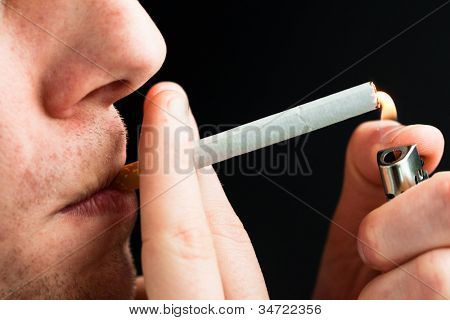 Man smoking against a black background