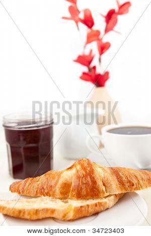 Desayuno con un croissant bisecado contra fondo blanco