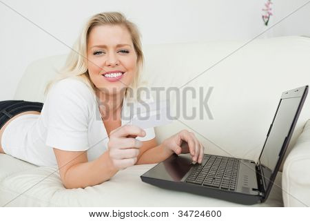 Casual woman lying on a white sofa with a credit card and a laptop