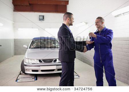 Mechanic giving car key while shaking hand to a client in a garage