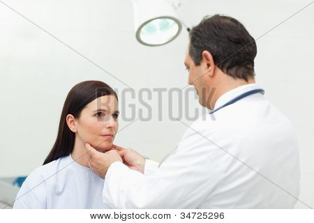 Doctor auscultating the neck of his patient in an examination room