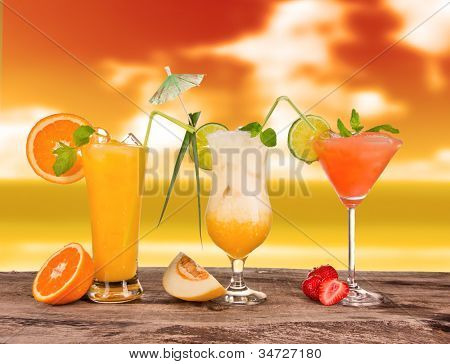 Summer cocktails in sunset with blur beach on background