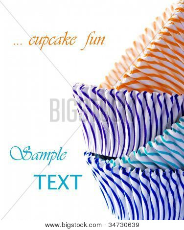 Colorful striped cupcake wrappers on white background with copy space.