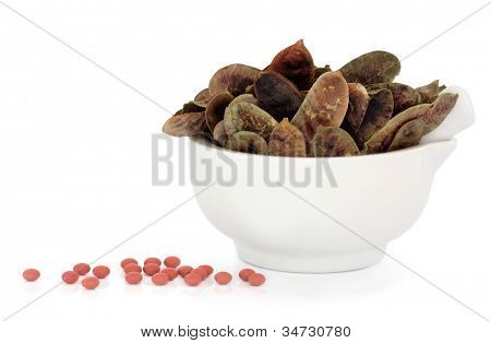 Senna pods in a porcelain mortar and pestle with loose tablets over white background. Alternative laxative remedy.
