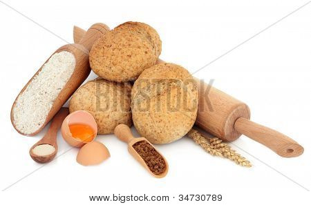 Wholegrain rolls with flour, eggs, brown sugar and yeast in wooden scoop and spoon with a rolling pin and wheat over white background.