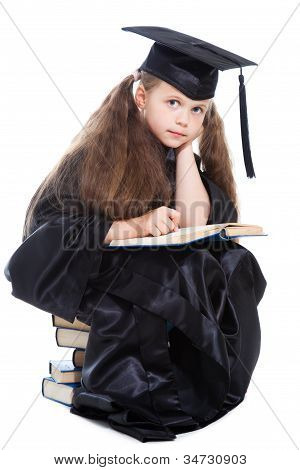 Girl In Black Academic Cap And Gown Reading Big Blue Book