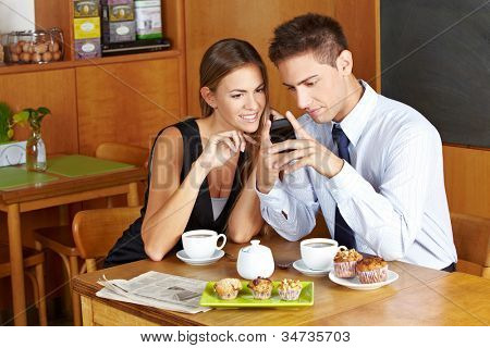 Business people in caf�© with smartphone having a meeting