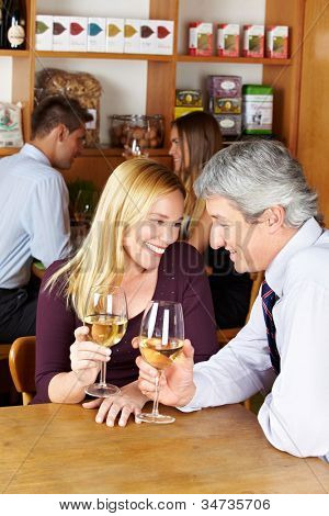 Elderly happy couple sitting with glass of white wine in a caf�©