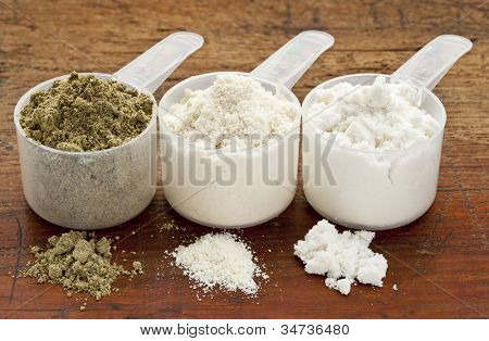 plastic measuring scoops of three protein powders (from left hemp seed, whey concentrate, whey isolate) on a grunge wood surface