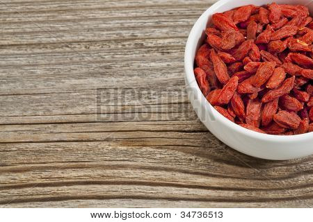 goji berries - white ceramic bowl on a grained wood, copy space