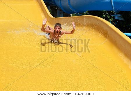 boy rolling with slide at water park