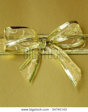 golden ribbon tied bow for holiday gold background