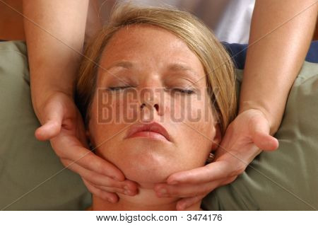 Massaging Face Of Young Woman At Wellness Center