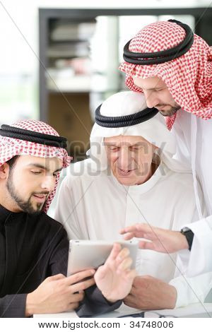 Arabic Business man with team mates working on tablet