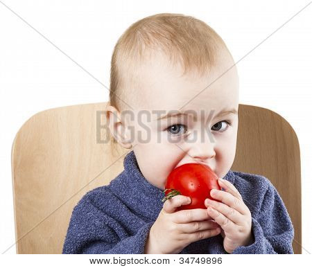 Young Child Eating Tomatoes In High Chair