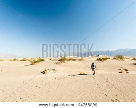 Man walking alone in the desert sand dunes