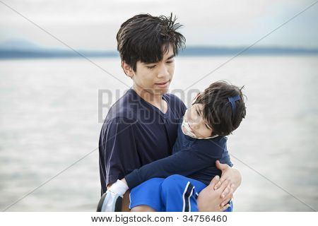 Big Brother Carrying Disabled Boy By Lake Shore